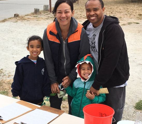 Local family with two small children smiling at the SGERC beach cleanup check-in tent.