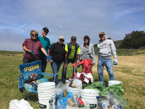 Group of SGERC volunteers smiling and presenting many buckets and bags full of trash collected at beach cleanup.