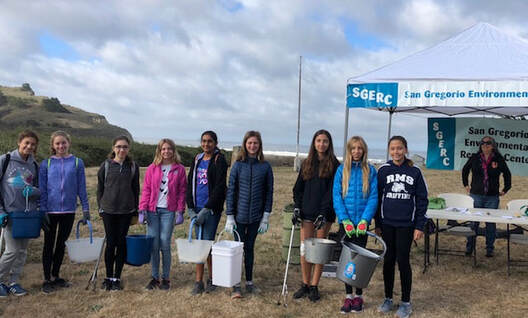 Group of young female volunteers smiling with gloves on and holding buckets, in front of SGERC check-in tent at beach cleanup..