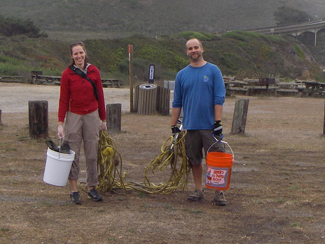Two Coastal Cleanup Day volunteers smiling and holding buckets to collect trash and ropes.