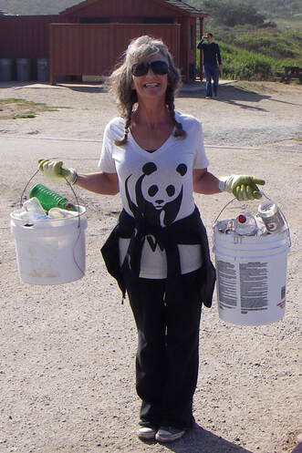 SGERC volunteer smiling while holding two buckets full of trash collected on Coastal Cleanup Day.