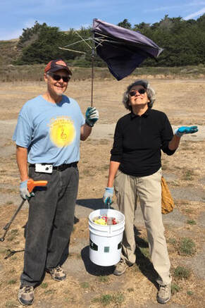 Trash collected at Beach Cleanup: Karl holds broken umbrella over Rita, holding her hand out like it's raining.