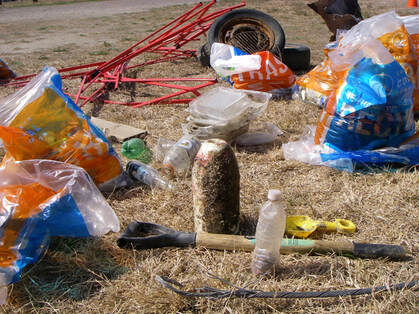 Trash collected at Coastal Cleanup Day is laid out on the ground; includes plastic bottles, containers, and kids' sand toys.