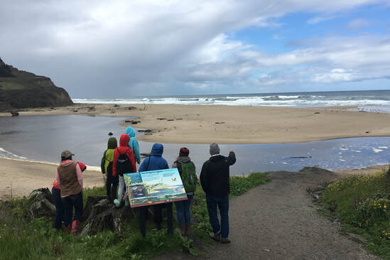 The class and volunteer behind the educational sign at San Gregorio State Beach, learning about the lagoon.
