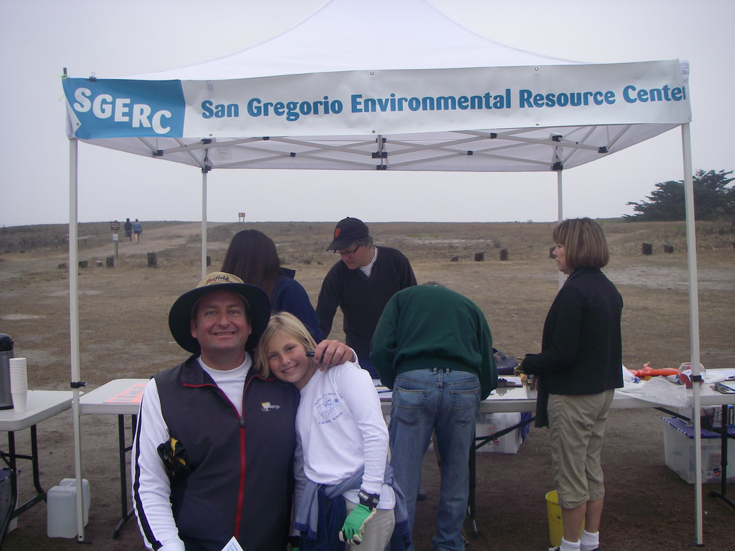 Two volunteers smile in front of SGERC beach cleanup check-in tent, while another volunteer checks people in under the tent.